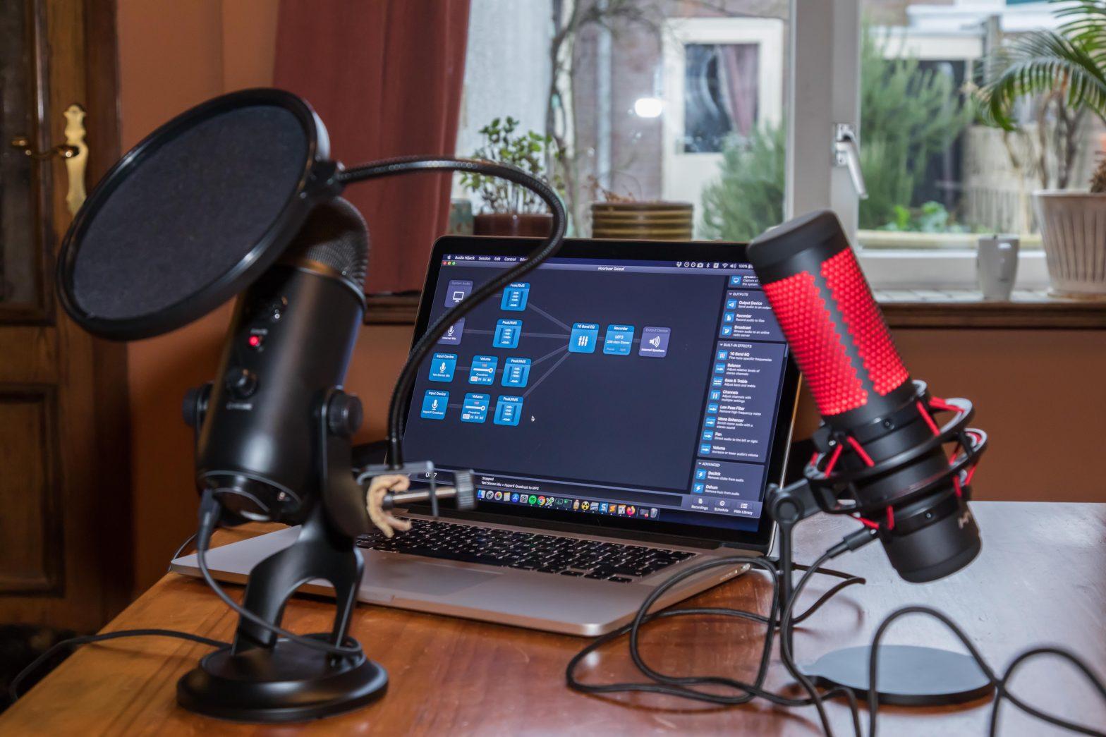 Twee studiomicrofoons op een tafel, met daarachter een macbook met op het scherm opnamesoftware.
