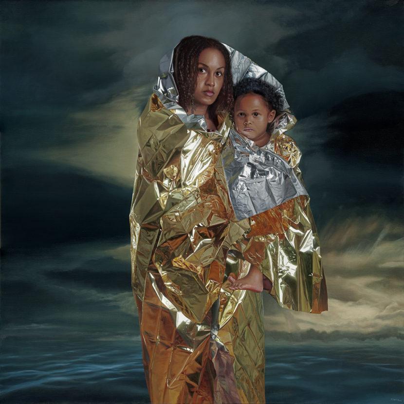 Een getinte jonge vrouw staat voor een donkere zee. Ze draagt een kind op haar arm. Beiden zijn verpakt in een isolatiedeken.